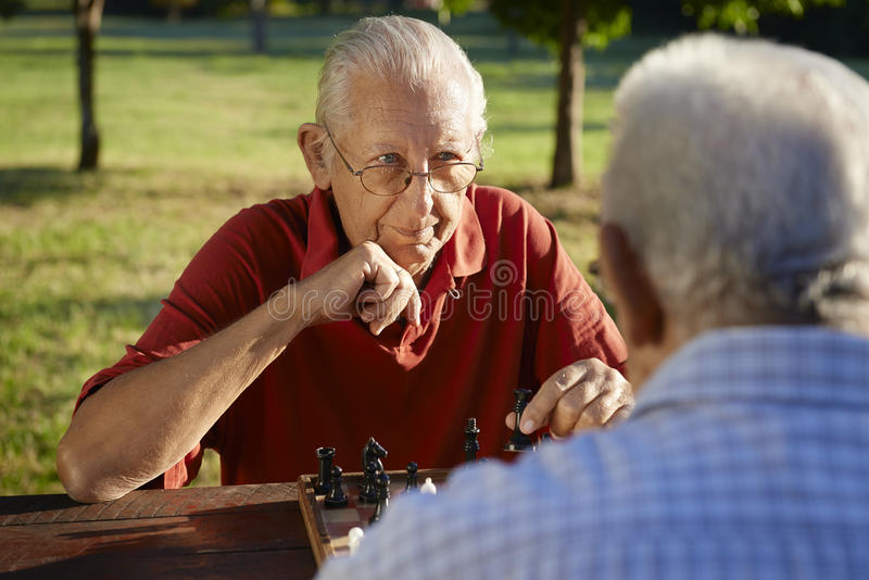 Active retired people, two senior men playing chess at park. Active retired people, old friends and free time, two senior men having fun and playing chess at royalty free stock photography
