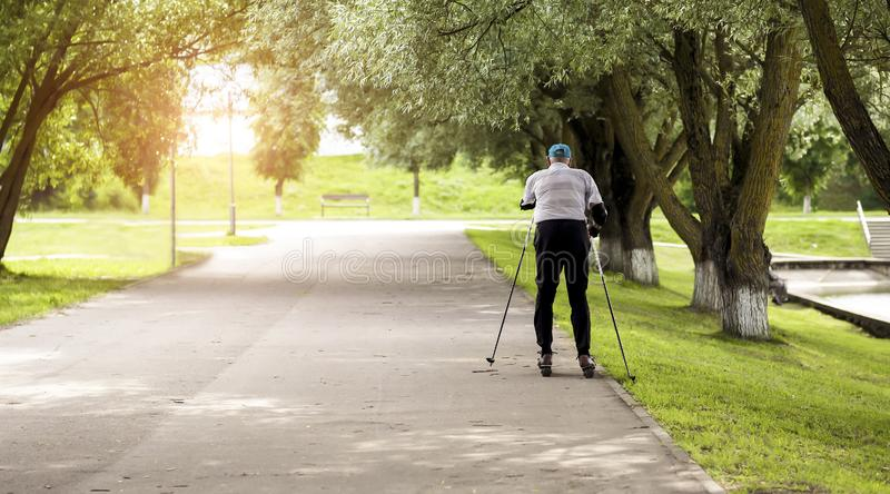 Active retiree rollerblading and making extreme turns. Autumn walks in the fresh air. Active old people stock images