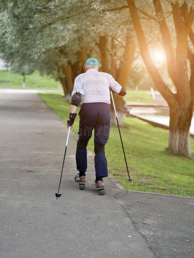 Active retiree rollerblading and making extreme turns. Autumn walks in the fresh air. Active old people stock image