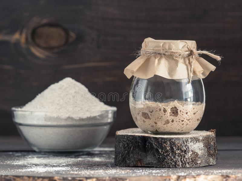 Rye sourdough starter and rye flour. Active rye sourdough starter in glass jar and rye flour on brown wooden background. Starter for sourdough bread. Toned image royalty free stock photo