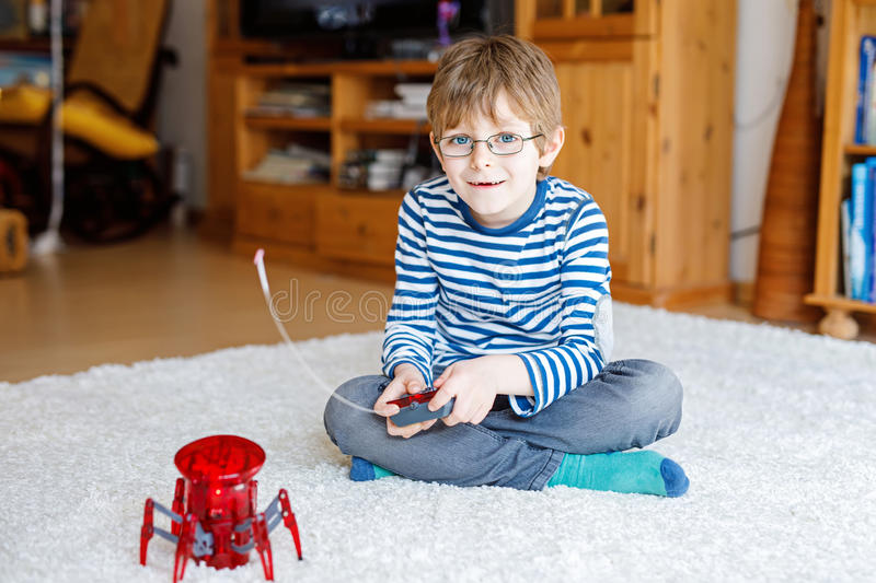 Active school boy with glasses playing with robot spider toy royalty free stock photo