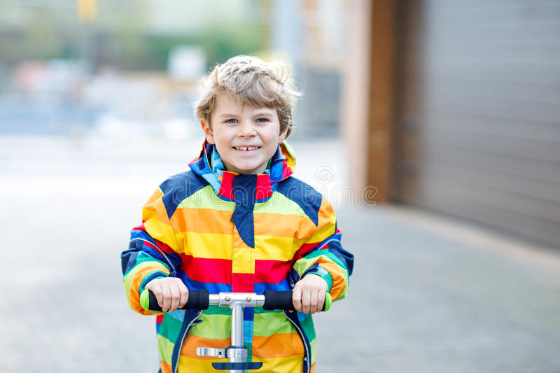 Active school kid boy in colorful casual clothes riding with his scooter in the city. Happy child in colorful clothes biking on way to school. or nursery stock image