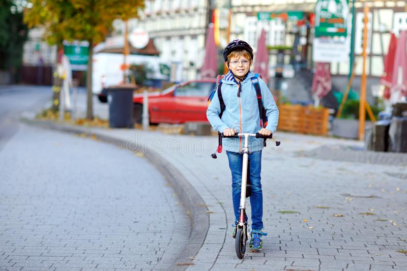 Active school kid boy in safety helmet riding with his scooter in the city with backpack on sunny day. Happy child in stock images