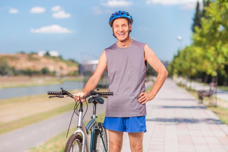 Active senior biker posing on a sidewalk stock photography