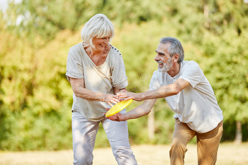 Active senior citizens playing frisbee. And having fun in the summer stock photos
