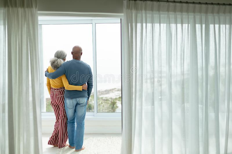 Active senior couple with arm around standing near window at home royalty free stock image