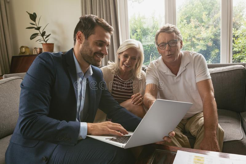 Active senior couple discussing with real estate agent over laptop in living room. Front view of active senior Caucasian couple discussing with real estate agent royalty free stock images