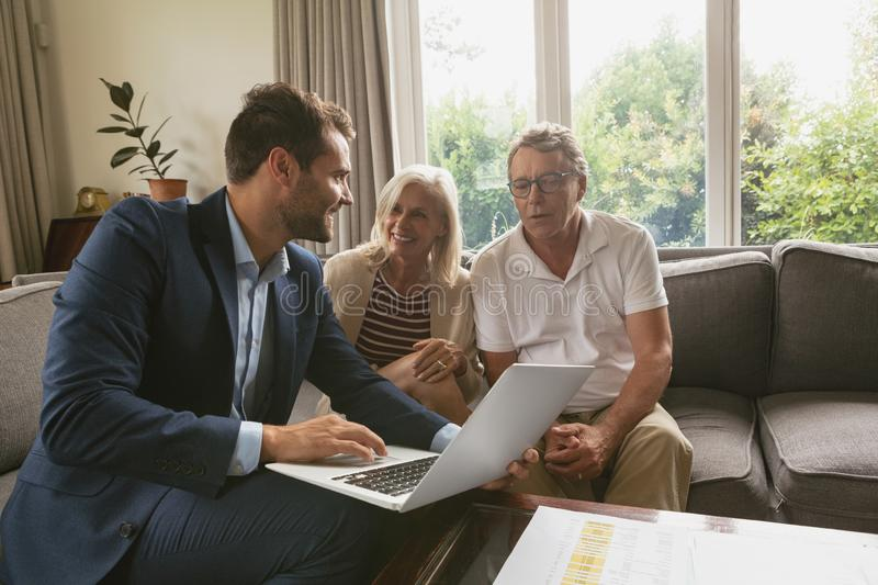 Active senior couple discussing with real estate agent over laptop in living room. Front view of active senior Caucasian couple discussing with real estate agent royalty free stock photography