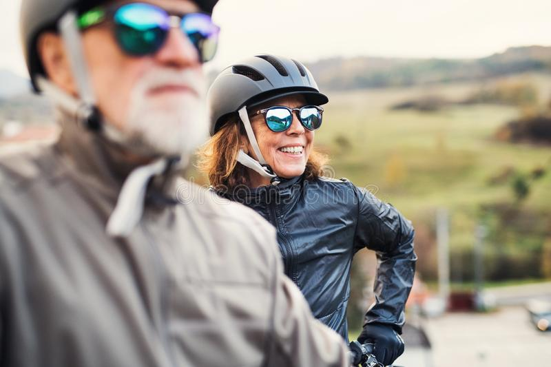 Active senior couple with electrobikes standing outdoors on a road in nature. stock photo