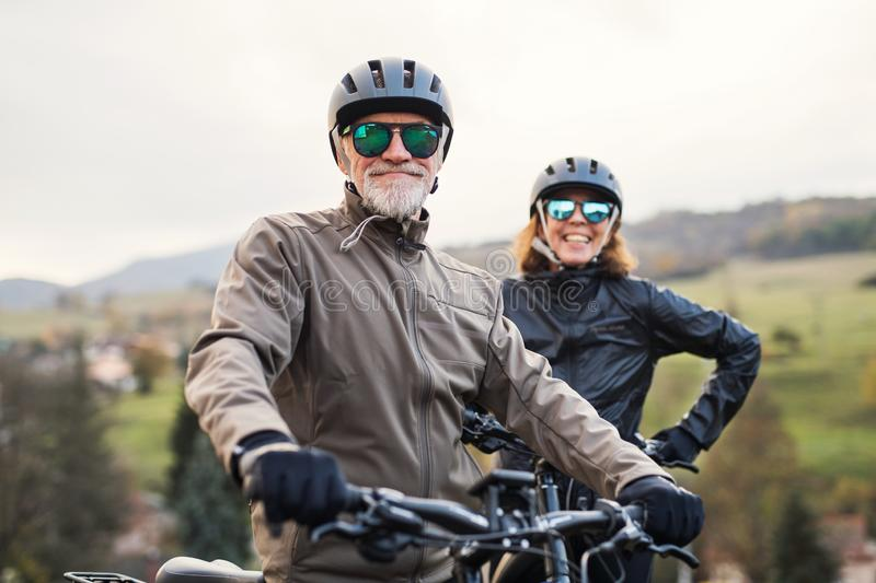 Active senior couple with electrobikes standing outdoors on a road in nature. royalty free stock photo