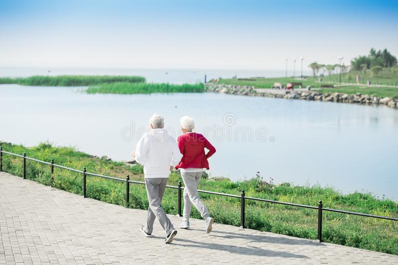 Active Senior Couple Running Along Lake stock photography
