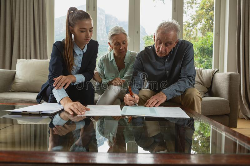 Active senior couple signing an agreement with real estate agent over documents in living room. Front view of active senior Caucasian couple signing an agreement royalty free stock photo