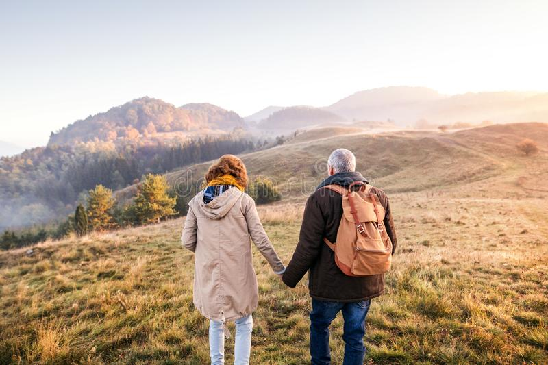 Senior couple on a walk in an autumn nature. royalty free stock photography
