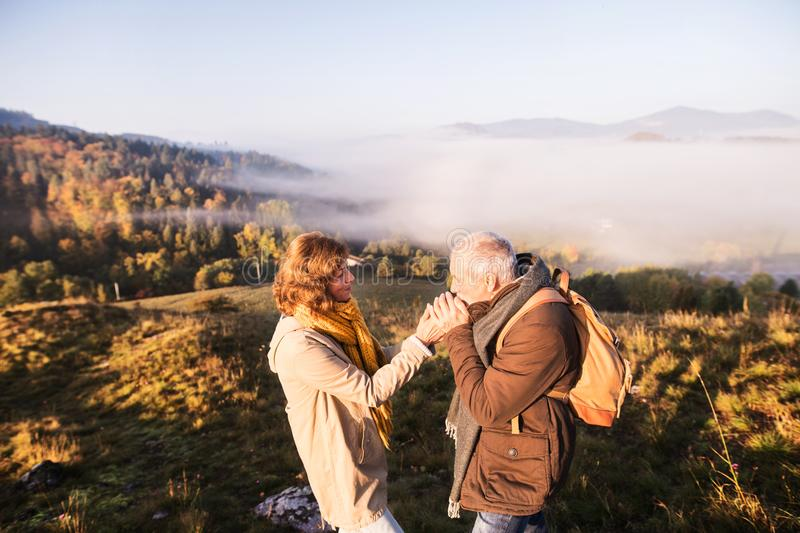 Senior couple on a walk in an autumn nature. royalty free stock photo