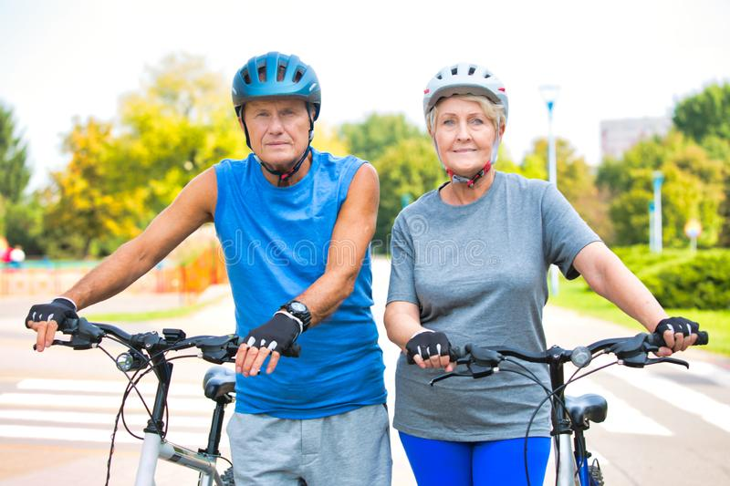 Active senior couple walking with bicycles in park royalty free stock photos