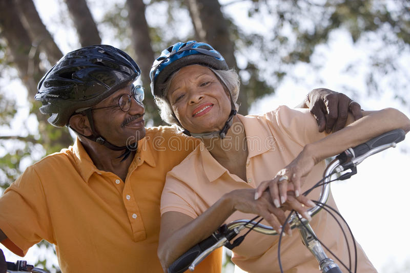 Active senior couple wearing cycling helmets and polo shirts, sitting on bicycles in park, man embracing woman, smiling stock image