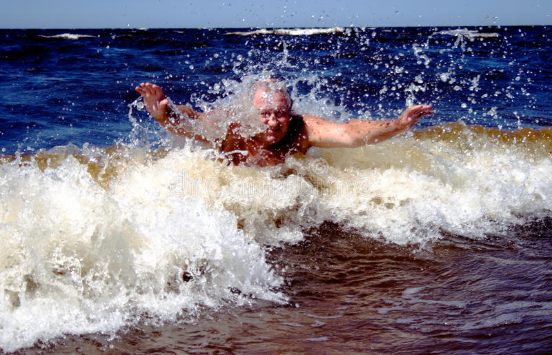 Active senior dives in waves royalty free stock photos