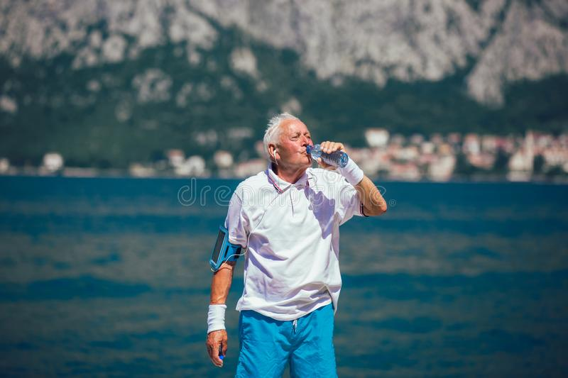Senior drinking water from bottle at the beach stock photos