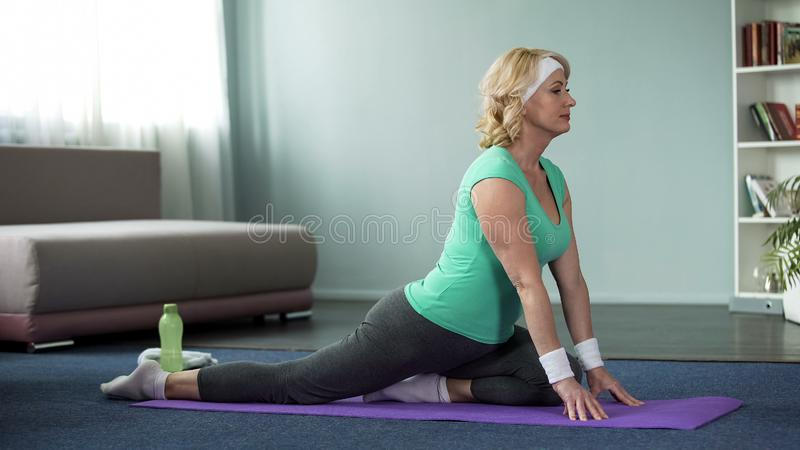 Active senior female practicing yoga on mat at home, healthy lifestyle, wellness royalty free stock photography
