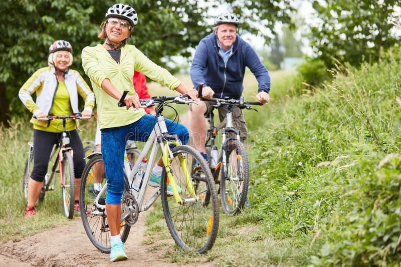 Senior group goes on a bike tour. Active senior group makes a bike tour in nature as a cycling holiday royalty free stock photography