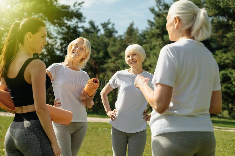 Active senior ladies chatting with their young coach stock photos