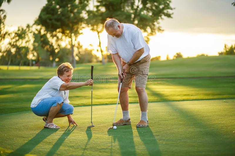 Active senior lifestyle, elderly couple playing golf together royalty free stock photos