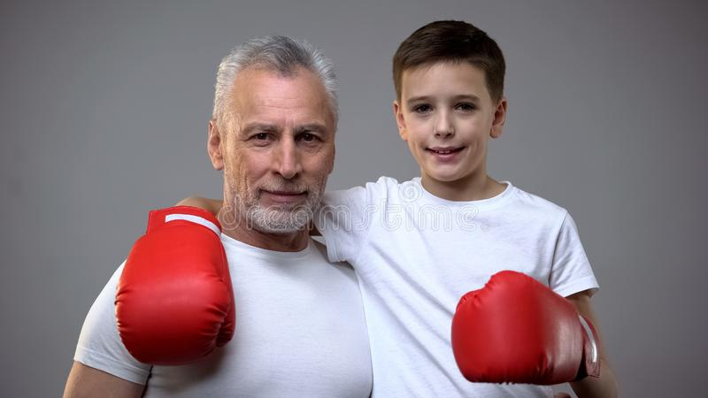 Active senior male and boy in boxing gloves looking to camera, healthy lifestyle stock image