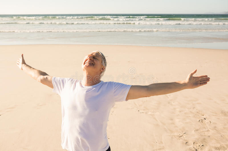 Active senior man with arms outstretched practicing yoga at beach royalty free stock photos
