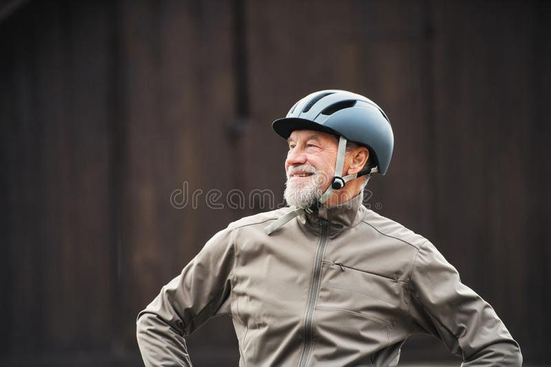 Active senior man with bike helmet standing outdoors againts dark background. stock photography