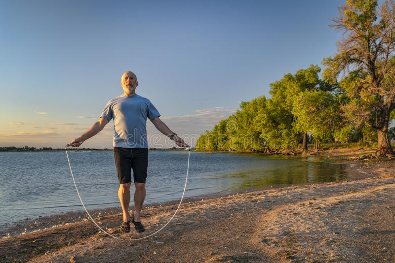 Senior man jumping rope on a beach. Active senior man is jumping a heavy fitness jump rope on a lake beach, Boyd Lake State Park in northern Colorado royalty free stock images