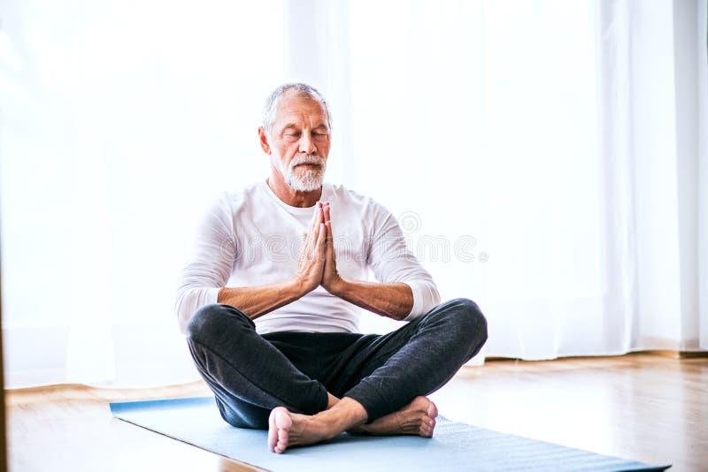 A contented senior man meditating at home. Active senior man meditating at home, eyes closed stock photos