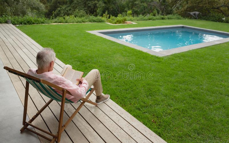 Active senior man reading a book while relaxing on sun lounger in the backyard royalty free stock images