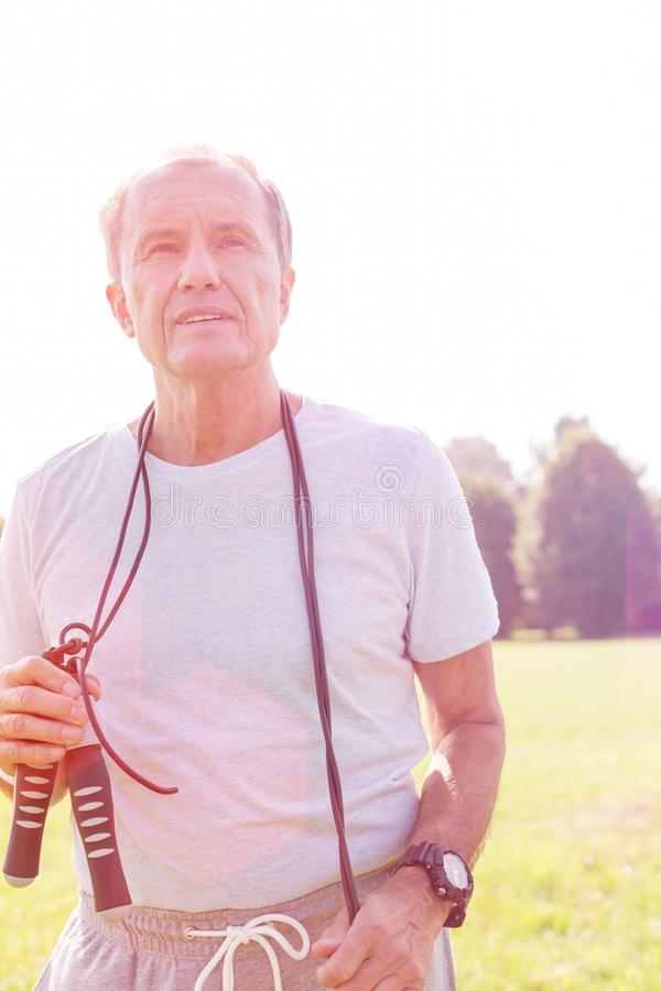 Senior man with skipping rope standing in park. Active senior man with skipping rope standing in park royalty free stock photos
