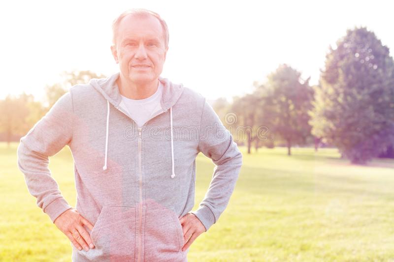 Active senior man standing with hands on hips in park royalty free stock images