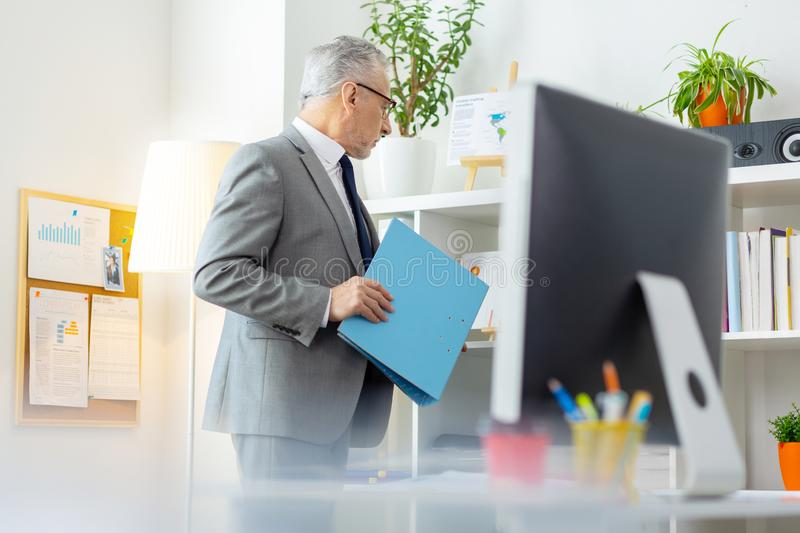 Active senior office worker taking blue fold from the shelves royalty free stock image