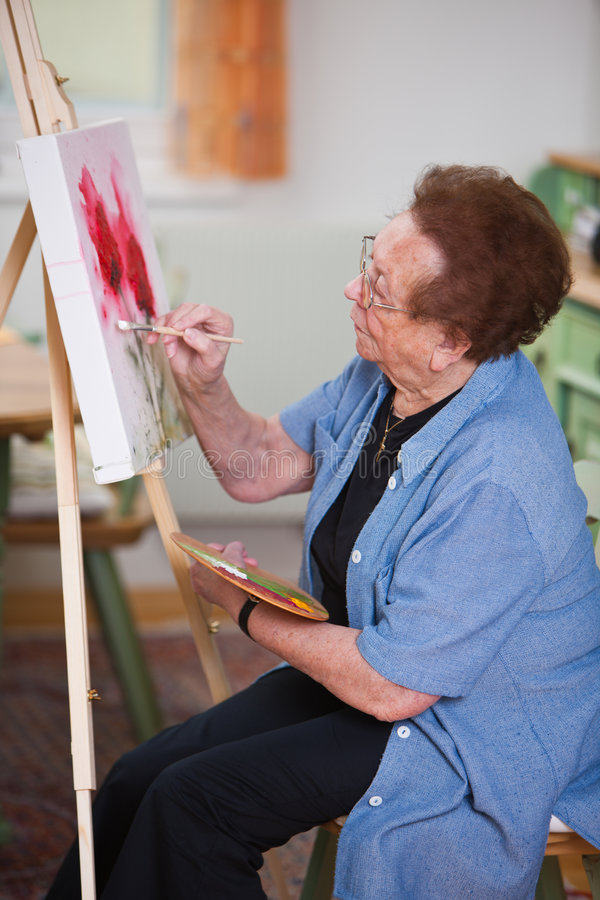 Active senior paints a picture in Leisure. Old woman paints a picture stock image