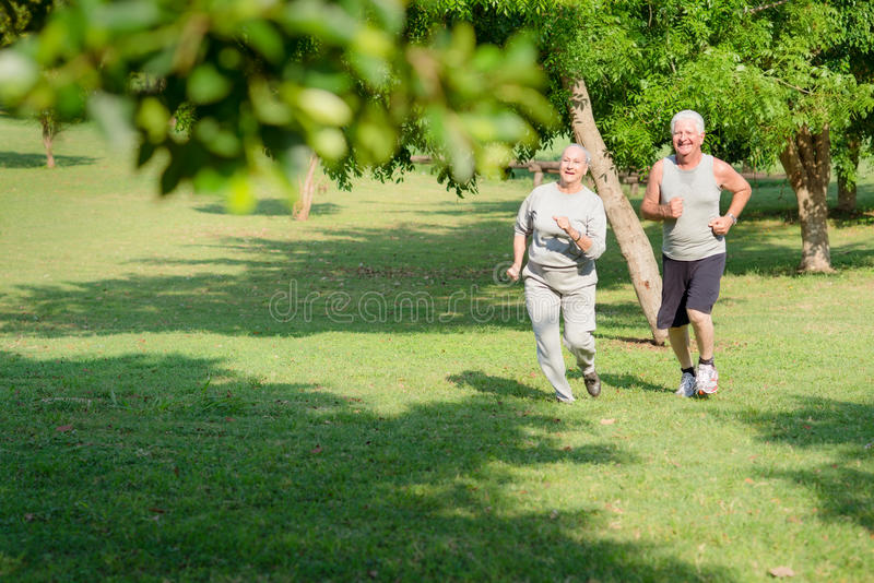 Active senior people jogging in city park royalty free stock photo