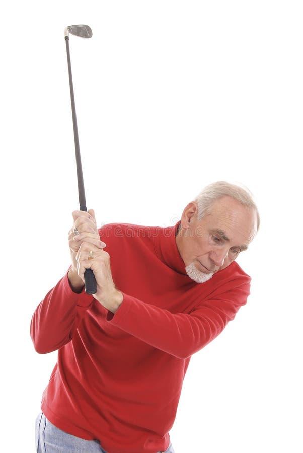 Active senior swinging golf club stock images