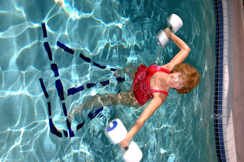 Active senior woman. An attractive smiling senior woman doing exercises in the pool stock photo