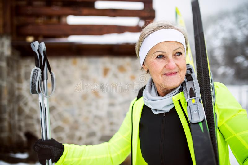 Senior woman getting ready for cross-country skiing. Active senior woman getting ready for cross-country skiing. Winter time royalty free stock images