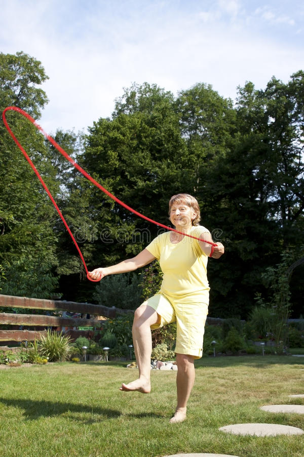 Active senior woman is jumping rope royalty free stock image