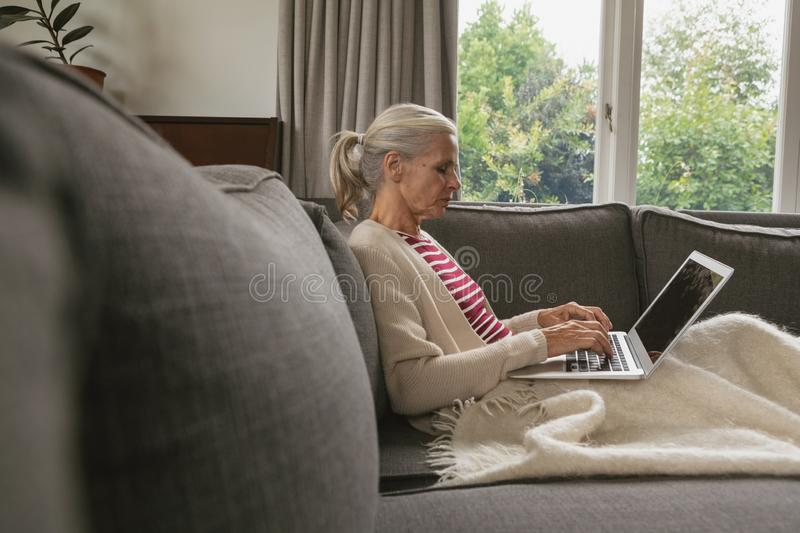 Active senior woman relaxing on sofa and using laptop in living room at comfortable home stock photo