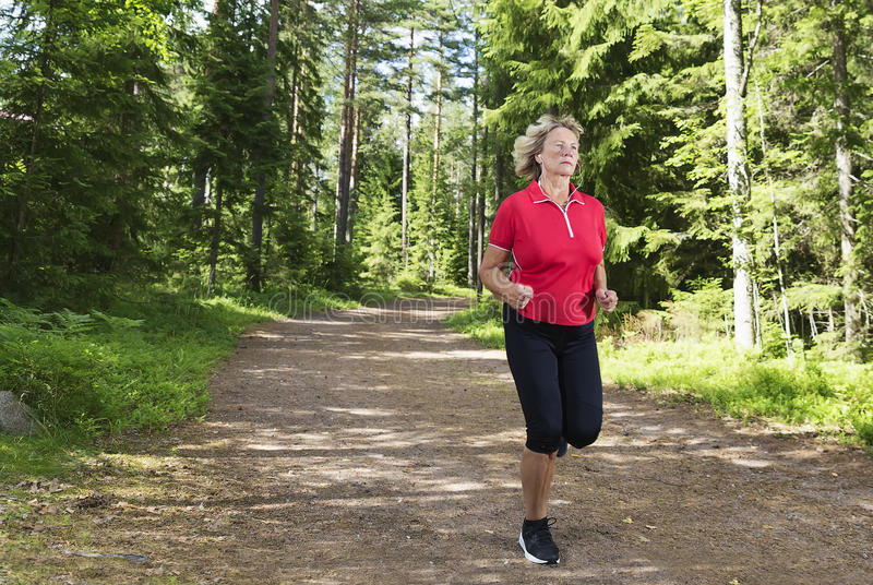 Active senior woman running at forest jogging track royalty free stock photography