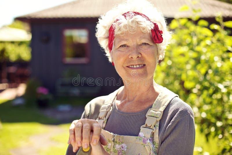 Active senior woman standing in backyard garden stock photo