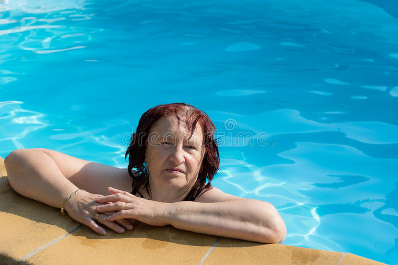 Active senior woman in a swimming pool royalty free stock image