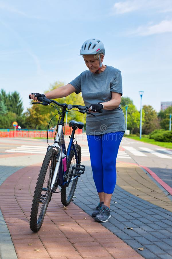 Active senior woman walking with bicycle in park stock images