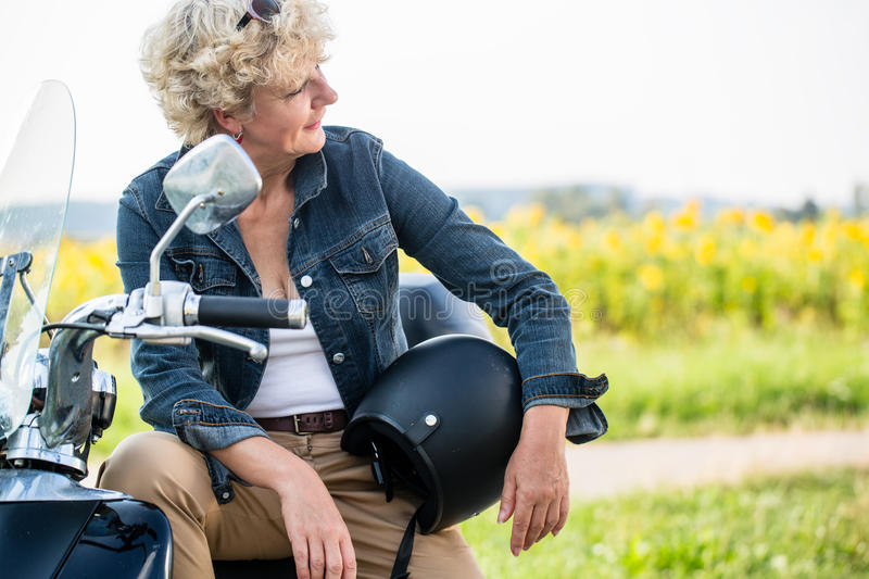 Active senior woman wearing a blue denim jacket while sitting on stock images