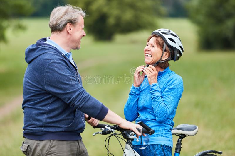 Senior woman puts on a bicycle helmet. Active senior women puts on a bicycle helmet with partner before the bike ride royalty free stock photos