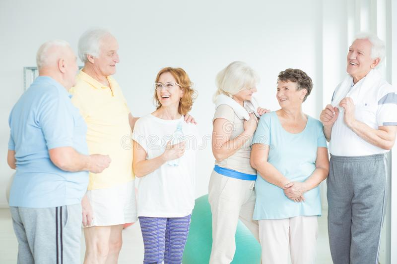 Active seniors concept. Group of elderly men and women laughing together at the gym wearing sports clothes stock image