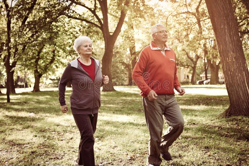Active seniors couple having recreation together in park. stock images